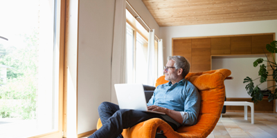 Older man sitting in a bright orange chair with his laptop in his lap, looking out the windown.