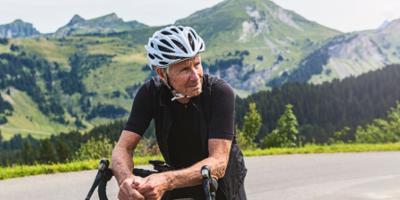 Senior man out biking along a beautiful mountainside background.