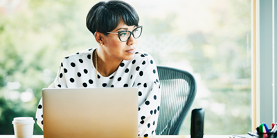 African American woman in polka-dotted shirt looking away from what she is studying on the computer.