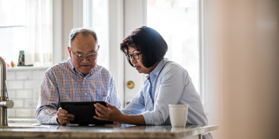 An Asian American couple reviews their social security and retirement planning goals while sitting in their kitchen.
