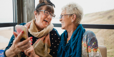Two elderly women laughing and enjoying a photo on a mobile phone.