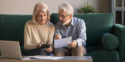 A senior adult couple reviewing their retirement accounts and accounting for costs and expenses.