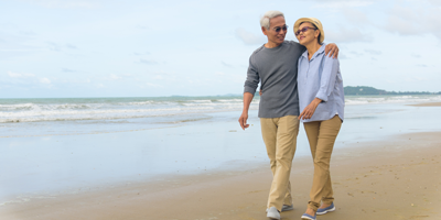 A senior adult couple walking along the beach and laughing because they have planned well for their retirement.