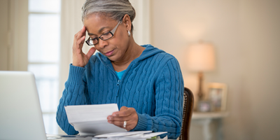 A senior African American woman reviewing her pension paperwork while deciding who to make her beneficiary.