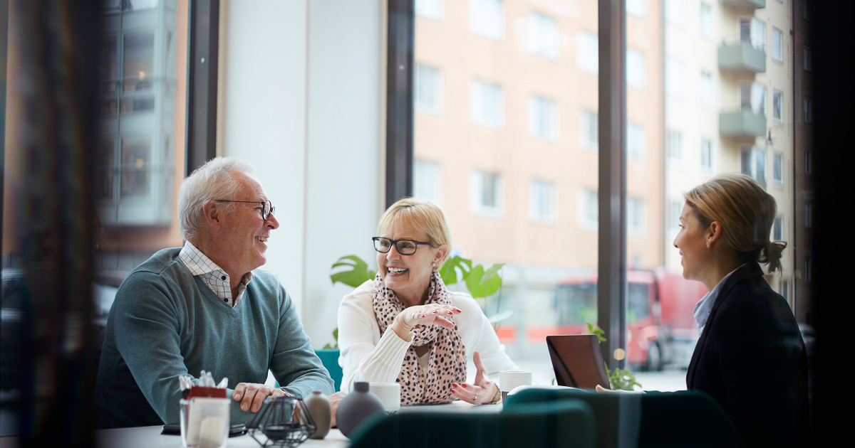 Older couple at a table with female financial advisor.