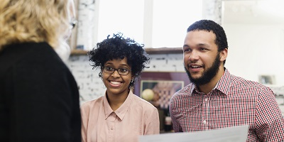 Smiling young couple talking with financial advisor