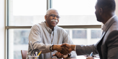 Senior man shaking hands with financial advisor across desk