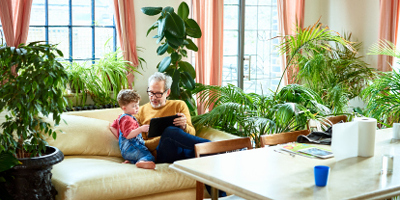 Grandfather and grandson on couch surrounded by indoor plants looking at a tablet screen.