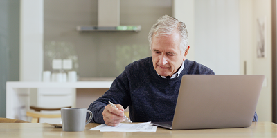 Senior man doing taxes on laptop at kitchen table
