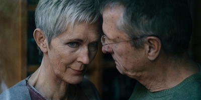 Older couple standing face-to-face with serious expressions.