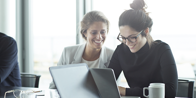 Two female coworkers smile while looking at laptop