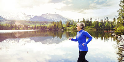 Senior woman running next to lake with pine trees and mountains in the distance