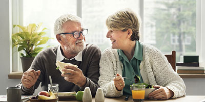 Older couple talking over breakfast about health savings accounts and retirement