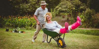 A senior couple playfully outdoors doing yard work.