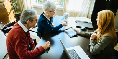 Senior couple sitting at financial advisor's desk looking at a tablet