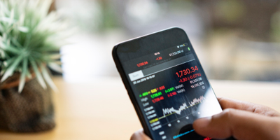 Person holding smartphone with screen displaying stock market graphs
