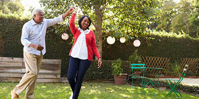 Photo of senior couple dancing outside in their yard