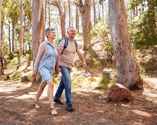 Senior couple walks through the woods together on a hike