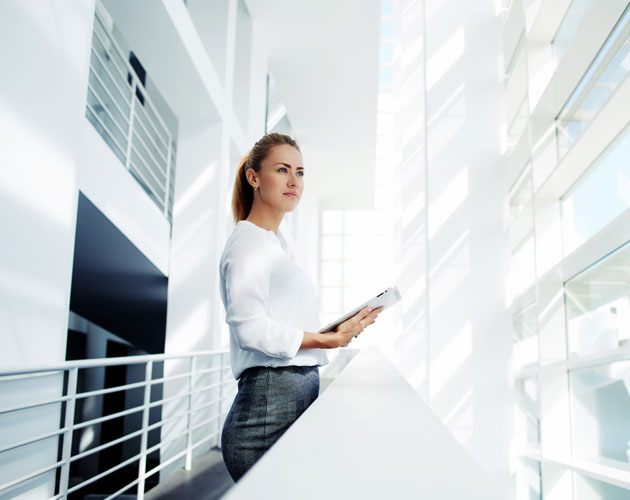 Young business woman looks out of modern office building