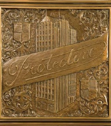 A golden memento reading Protective across a drawing of the old Protective Life building in downtown Birmingham.