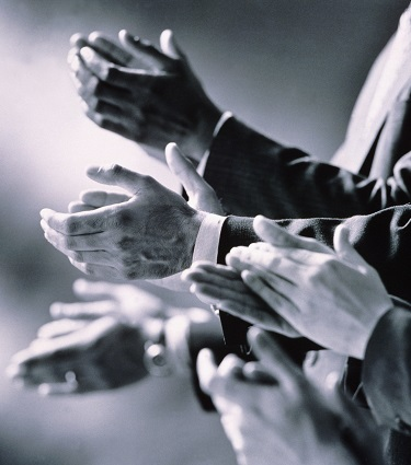 A black and white photo of businessmen clapping as if to celebrate.