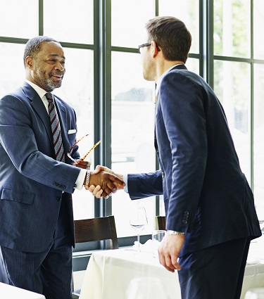 Two businessmen shaking hands as if to close a deal.