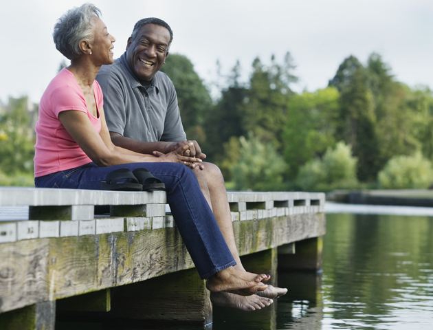 Older African-american couple sitting on dock laughing