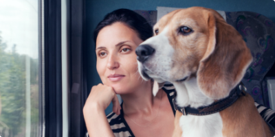 Woman gazes through a window with her dog