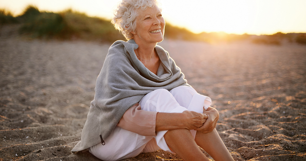 Smiling senior woman sitting on a beach.