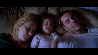 Mom, dad and young daughter in bed right before the alarm goes off in the morning